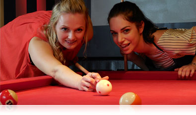 Close-up photo of two women playing billiards
