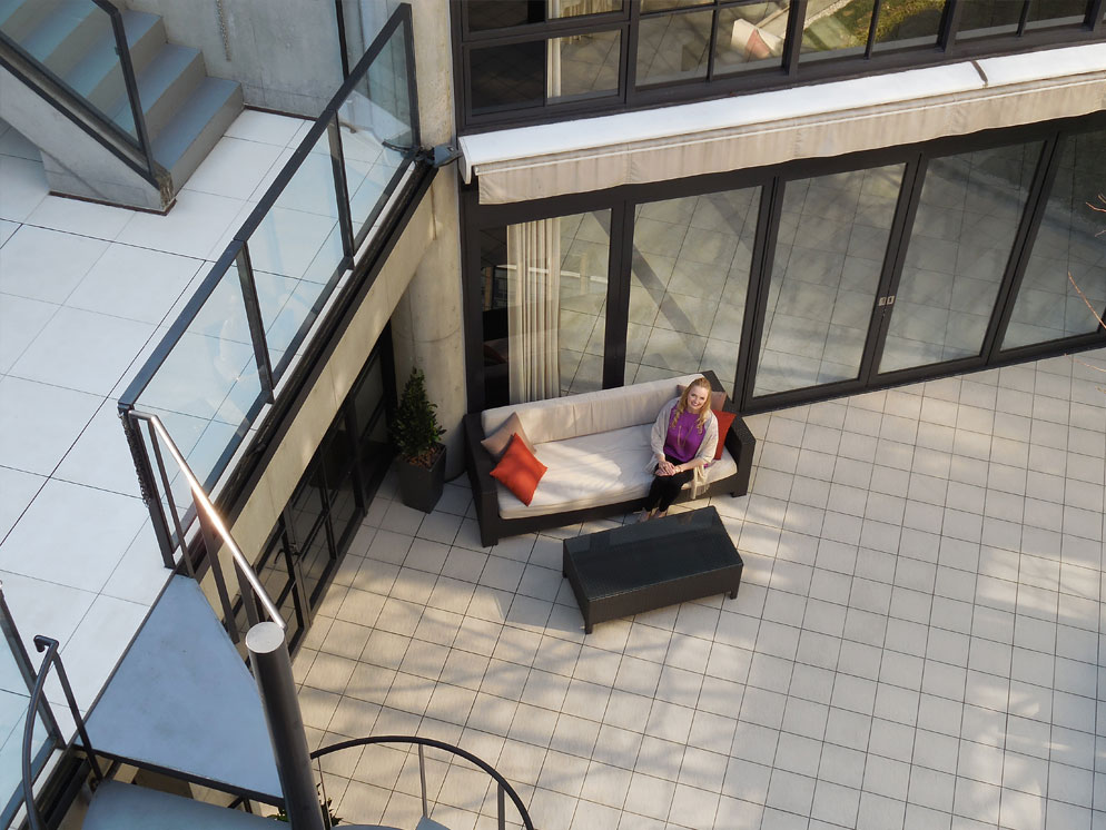 zoomed in shot of a building and its patios, with a woman on a couch