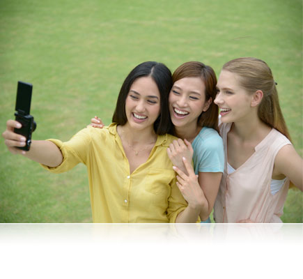 Photo of three ladies looking at the S6900, held in one of the lady's hands, taking a selfie