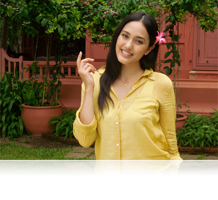 COOLPIX S6900 photo of a woman wearing a yellow shirt with a pink flower in her hair