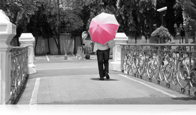 COOLPIX S6900 photo of a person walking over a bridge with a pink and white umbrella, and the rest of the scene is in B&W