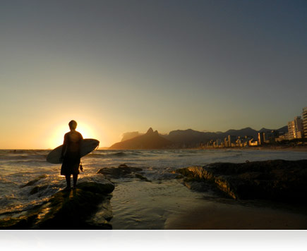 Photo of the sun setting over Rio De Janeiro, Brazil while a surfer stands in the shore break