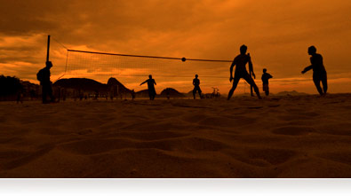 Photo of beach volleyball players at sunset