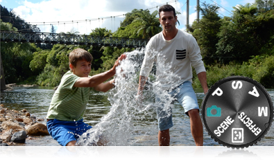 Photo of a dad and son having fun at the lake's edge