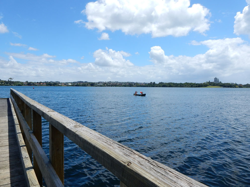 Zoom slider - ultra wide view of a dock and lake with a small boat in the center
