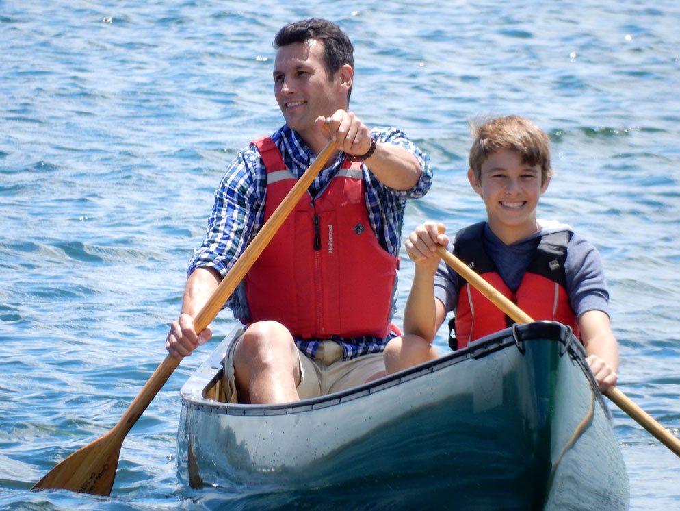 Zoom slider - Canoe with dad and son filling frame, showing them smiling
