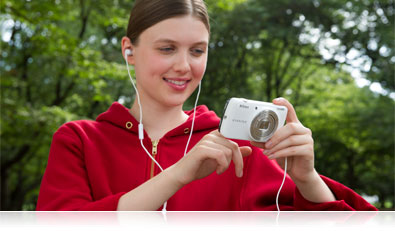 Photo of a woman in a red sweatshirt and headphones plugged into the COOLPIX S810c listening to music on the camera