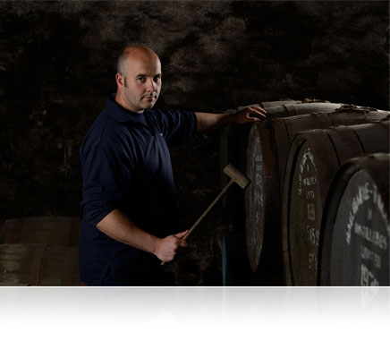 Low light photo of a man with barrels of alcohol shot with the Nikon Df