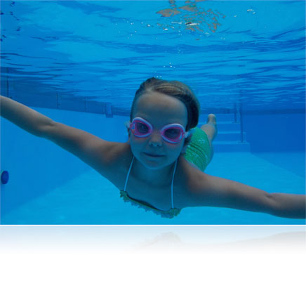 Underwater photo of a girl in a pool looking at the camera