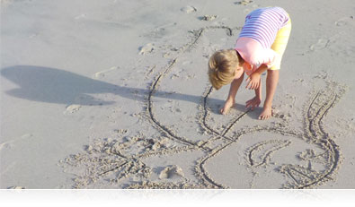Photo of a boy on the beach, drawing in the sand highlighting scene modes
