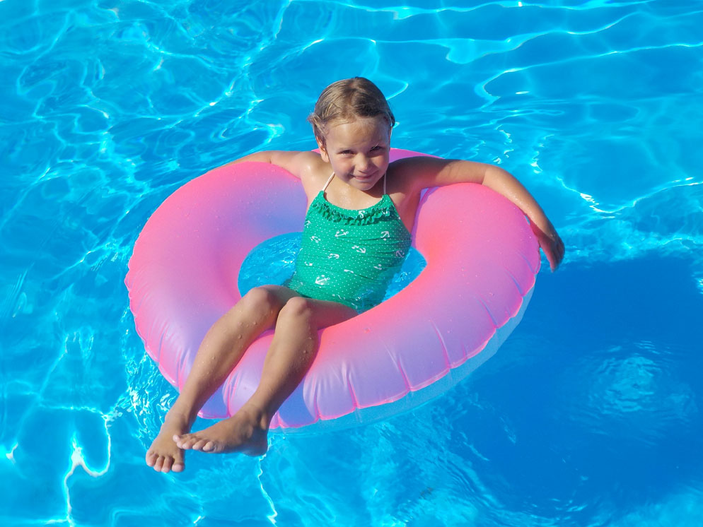 Wide shot of a girl on a floating ring in a pool showing the zoom range of the S32