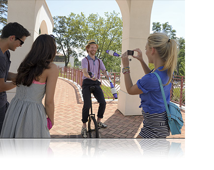 Photo of a woman and friends watching a unicyclist juggle as she takes a photo with the COOLPIX S02
