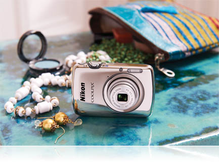 photo of the COOLPIX S01 with contents of an open purse on a table