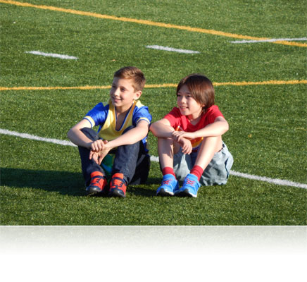 Photo of two young boys sitting on the grass of a soccer field