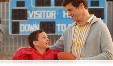 Photo of a boy in wearing football gear and his dad holding a football