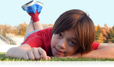 Photo of a boy lying on the grass on a soccer field, looking at the camera