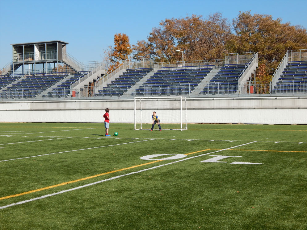 wide shot of two boys on a soccer field at the goal