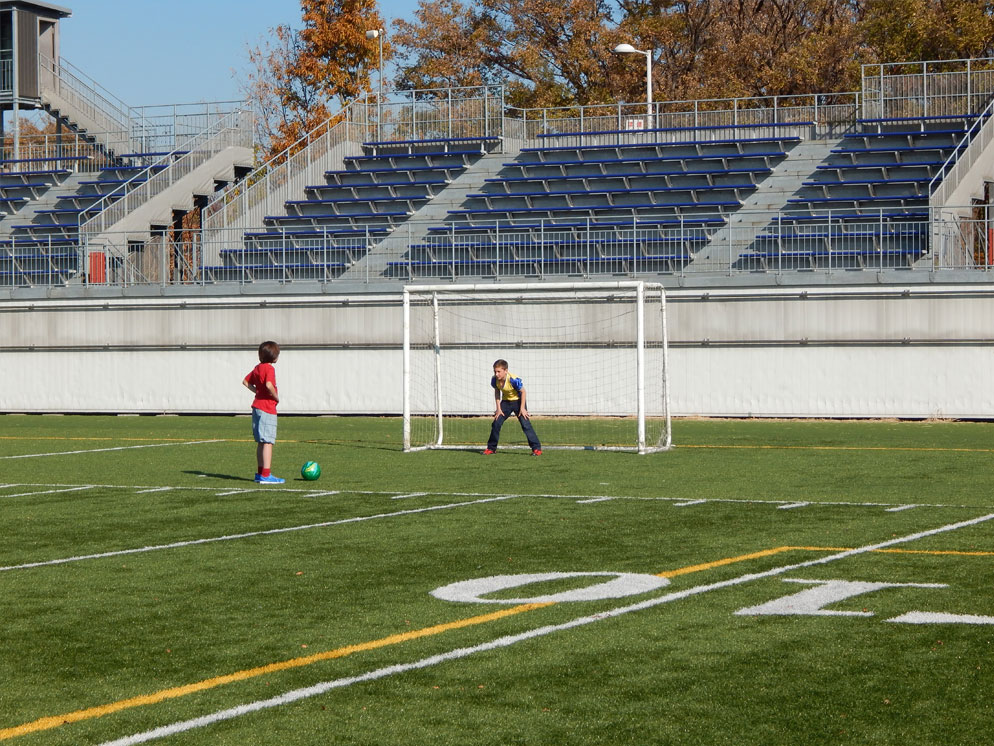 Photo of two boys on a soccer field, one kicking the ball to the other in the goal