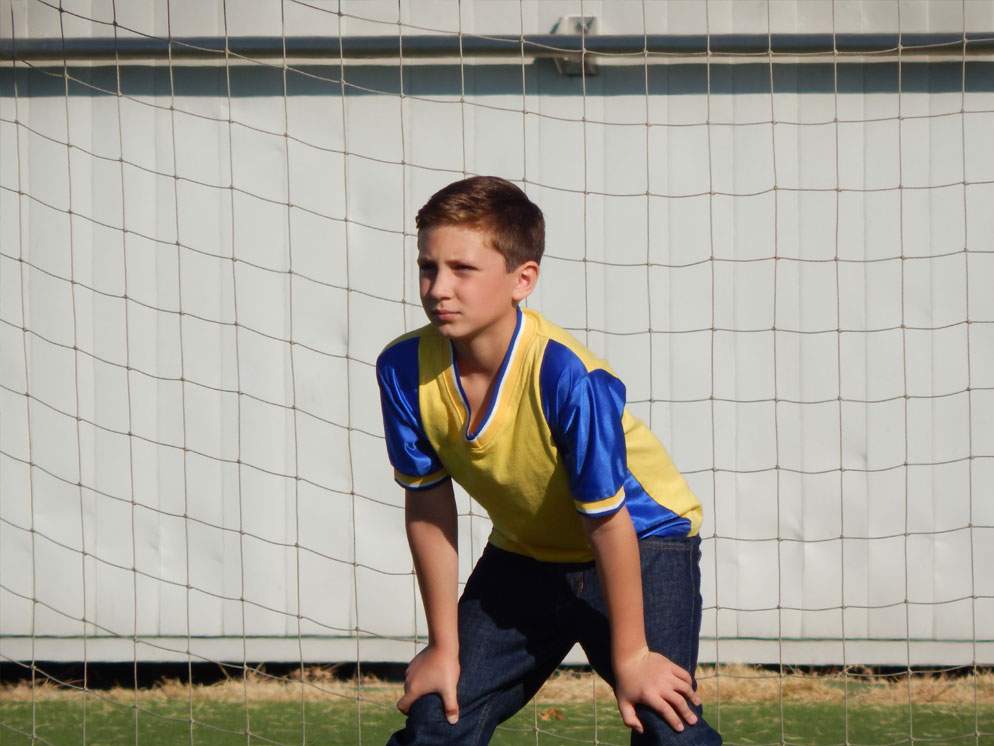 Photo of a boy in a soccer goal, waiting for the ball