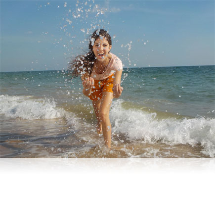 COOLPIX S33 photo of a girl in the surf splashing water at the camera