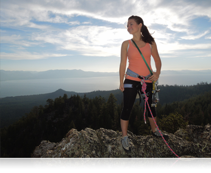 Photo of a woman rockclimber standing on a peak, backlit
