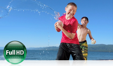 Photo of two boys having a water balloon fight at the shore