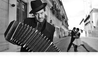 B&W photo of a musician with tango dancers in the street beyond