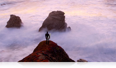 Photo of a surfer standing on a rock overlooking the water