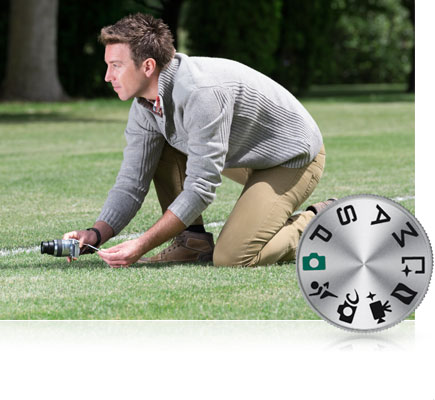 Photo of a man kneeling on the grass shooting at a low angle using the tilting touchscreen of the Nikon 1 J5 inset with the mode dial