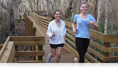 photo of two woman jogging on a raised deck in the trees