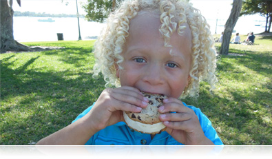 photo of a kid eating a cookie ice cream sandwich