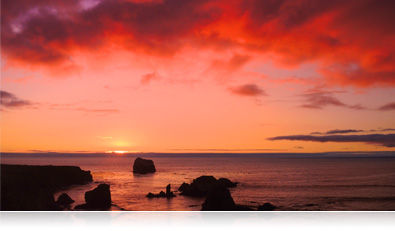 sunset photo of a rocky shoreline and deep red clouds