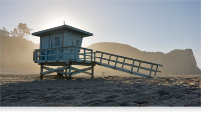 photo of a lifeguard stand on the beach with the sun backlighting it