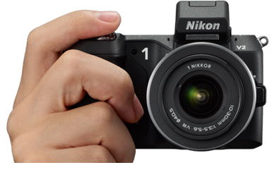 photo of a hand holding the Nikon 1 V2 with finger on the shutter button