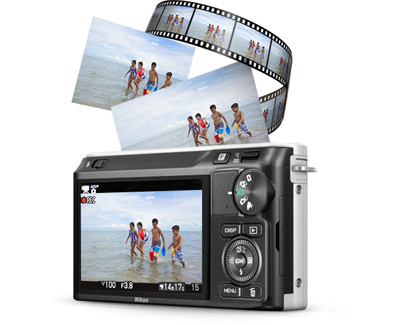 Rear of the Nikon 1 J2 with a shot of kids playing in the ocean on the LCD and in a filmstrip above the camera
