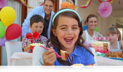 Photo of adults and kids enjoying cake at a birthday party