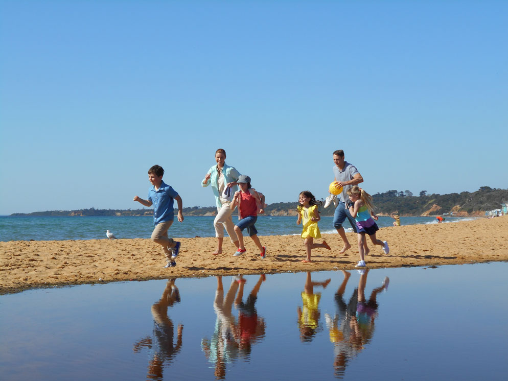 wide shot of a family running on the sand and their reflections in the water
