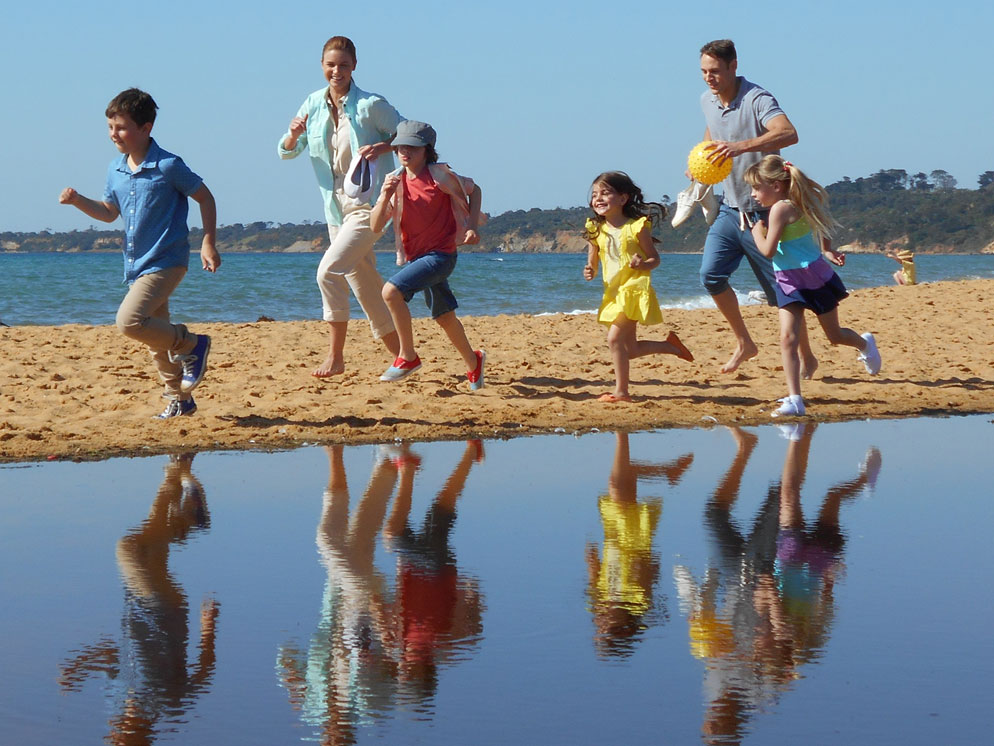 closer shot of a family running on the sand and their reflections in the water