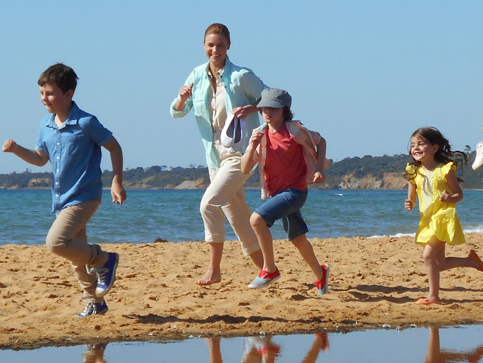 shot of a mom and three kids running on the sand