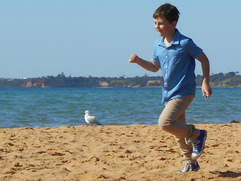 photo of a young boy running on the sand
