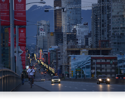 photo of a city street at dusk with mountains in the background