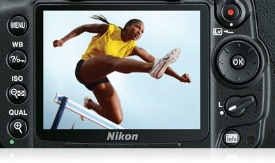 Photo of the rear of a D7000 camera body cropped tight on the LCD and surrounding buttons, with an image of a hurdle jumper on the screen