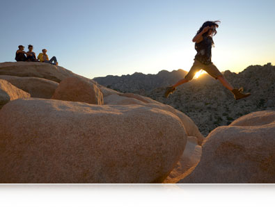 Nikon D7000 photo of a person jumping between large boulders with a group of people watching from the distance with inset example of the camera's ISO range