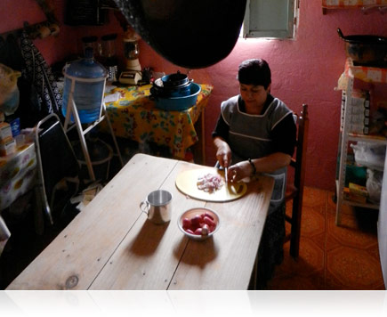 Low-light photo of a woman preparing food at her kitchen table