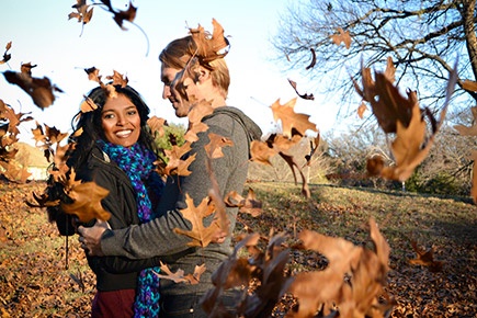 Dixie Dixon photo of a couple embracing, in a park in the autumn with leaves flying around them