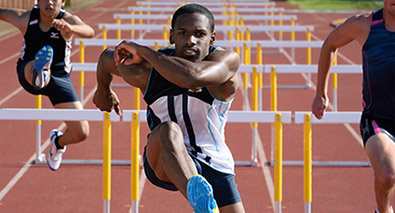 Photo of track and field athletes jumping over hurdles
