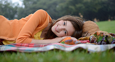 Photo of a woman lying on a blanket in a park looking at the camera