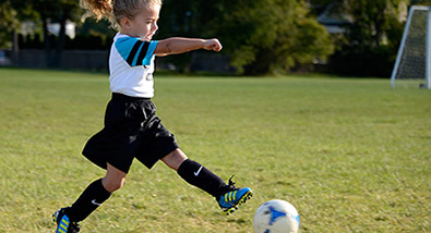 Photo of a young girl playing soccer on a field, kicking a soccer ball