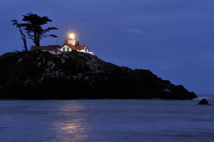 Photo of a lighthouse on a hill, overlooking the shore, taken at night