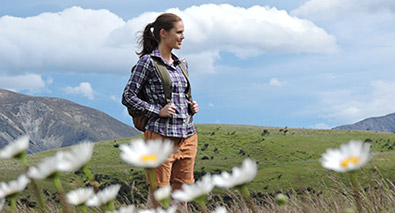 Photo of a woman in a field on a mountaintop, with daisies in the foreground and grass and sky in the background